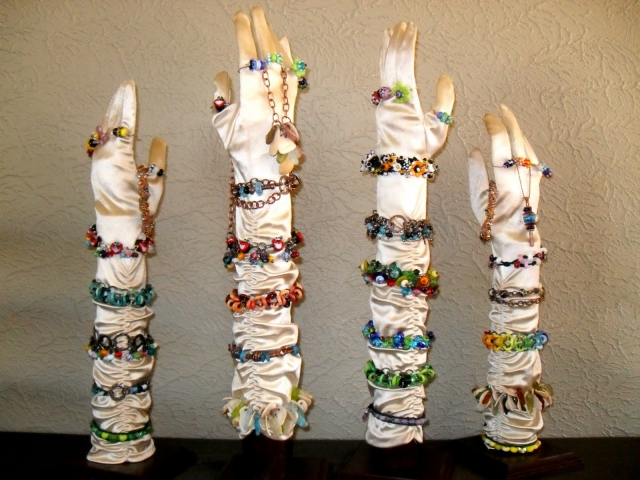 Using display hands with cream satin gloves as jewelry display ideas for craft shows and funky colored bracelets and rings.