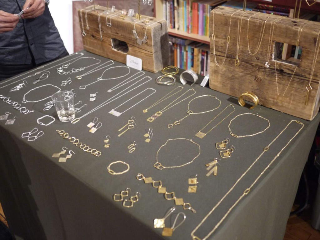 Nickel free jewelry displayed on a simple stand with a grey cloth on it, but also adding some all natural wood holders in the back.