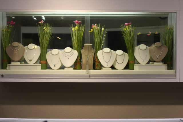 Rustic chic stand with flower and grass decoration inside a glass box, inspiration for jewelry display ideas.
