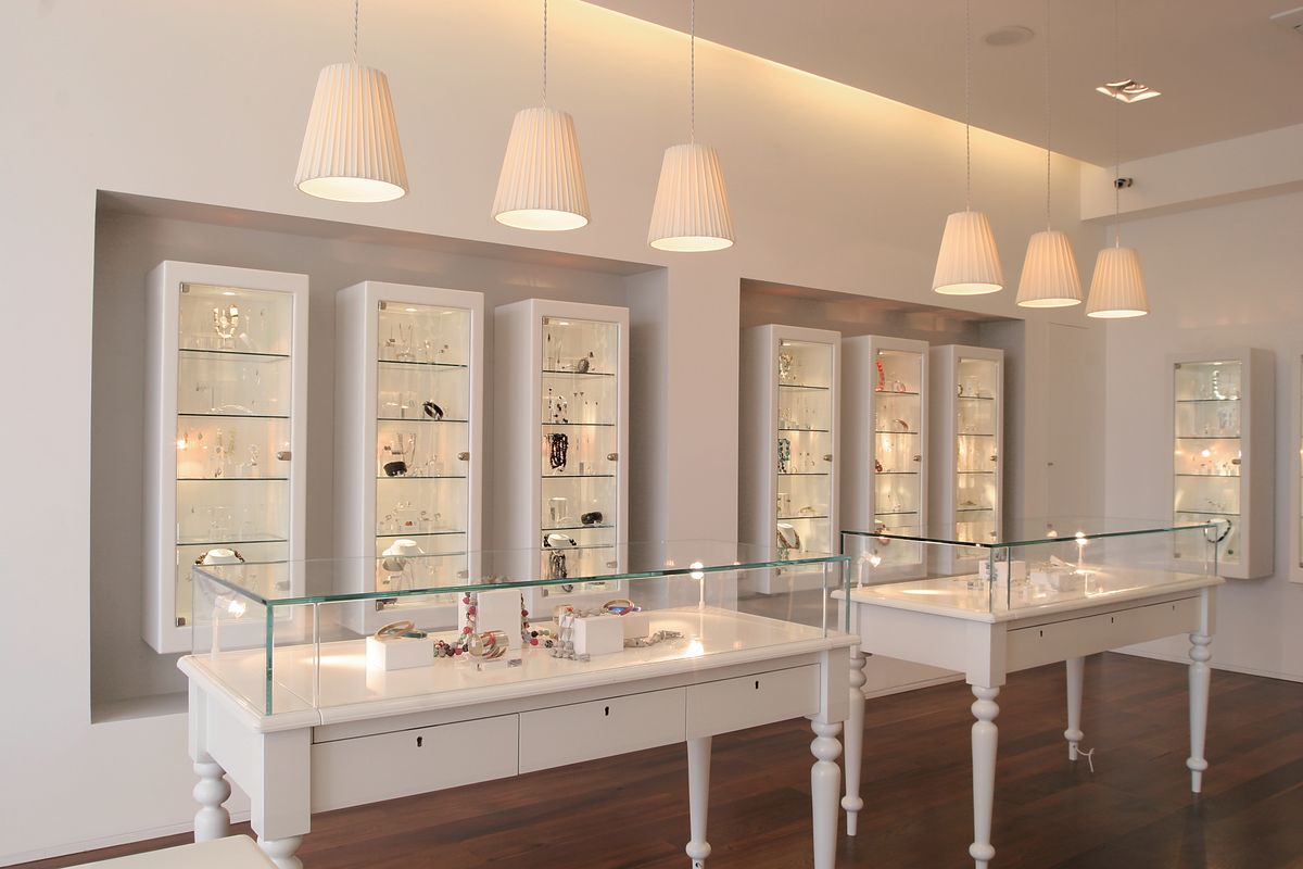 Jewelry display interior design with suspended lamps, white glass display stands and white display cabinets.