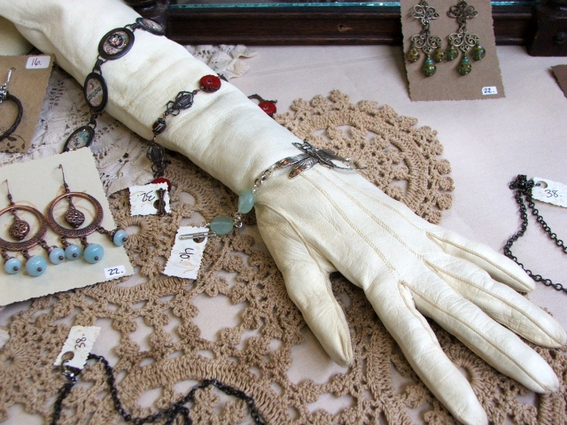 Jewelry display using a long leather glove and crochet patterns perfect for a vintage setting.