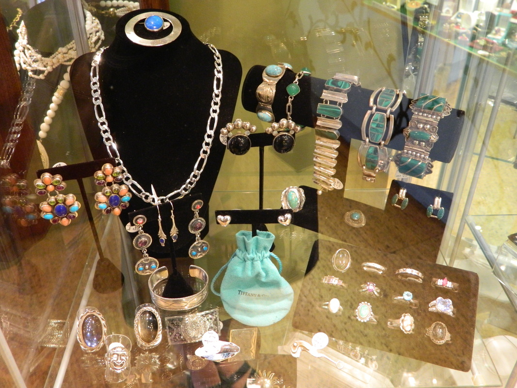 Jewelry retail display in a glass box, with holders for necklaces, bracelet racks and ring holders.