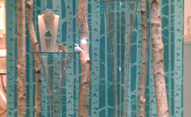 Anthropologie Christmas window display with thin tree trunks and plant decoration combined with beautiful jewelry.