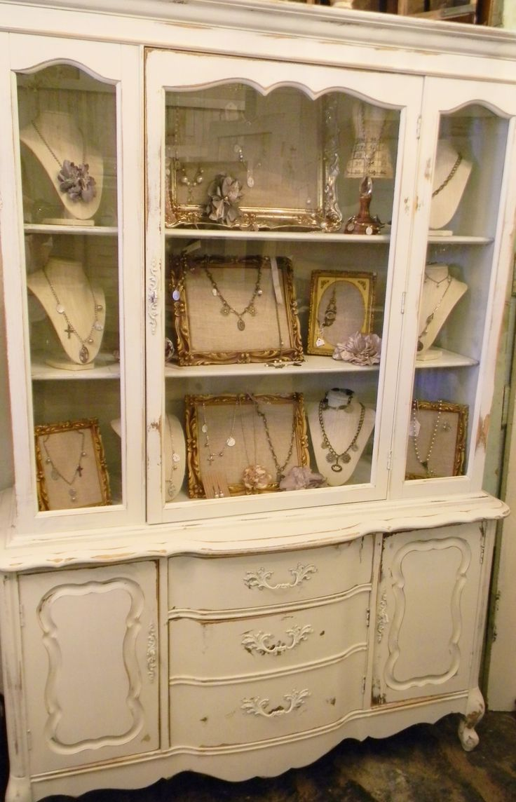 Antique furniture piece with glass display and drawers, a shabby chic paint shelf jewelry display idea.