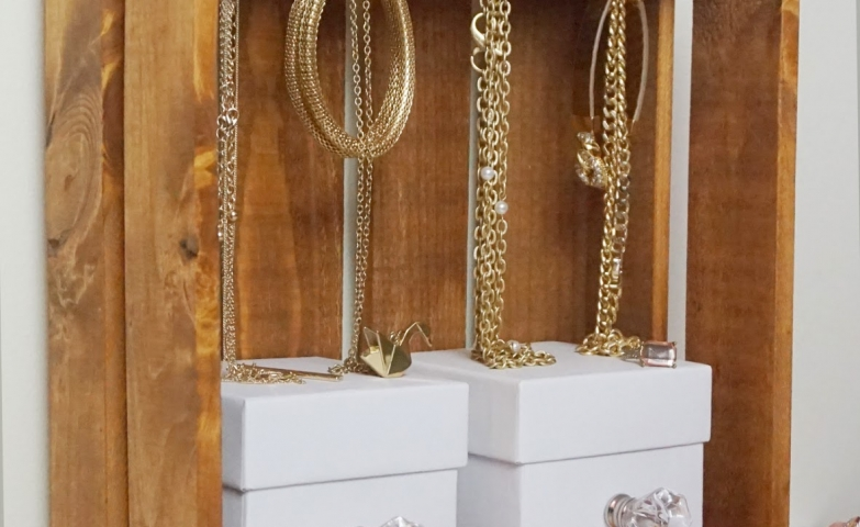 Awesome jewelry storage display design made from a wooden box with build-in hooks for hanging and some small white boxes added for additional storage.