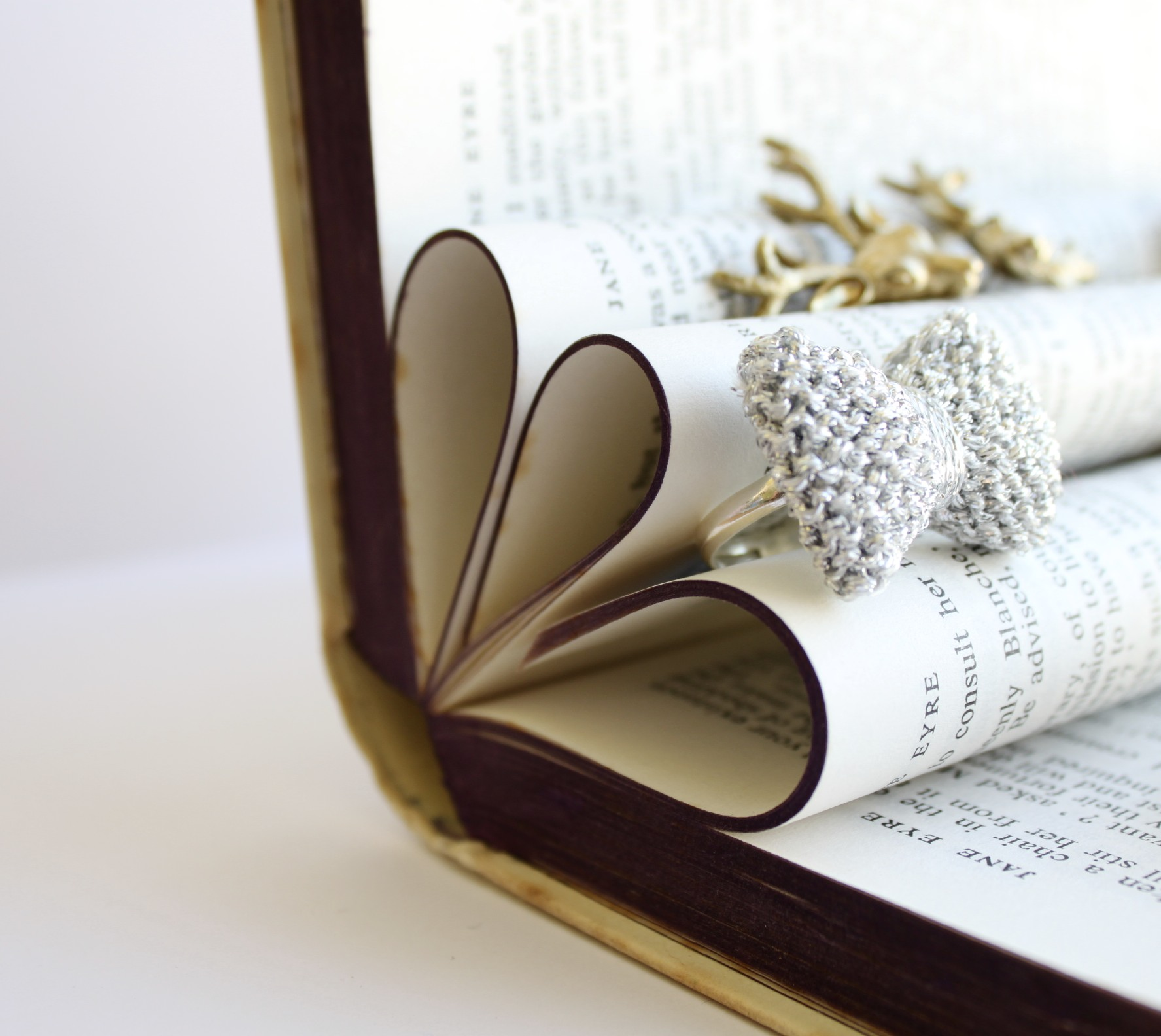 Jewelry display easy to make by bending multiple pages from a vintage looking book.