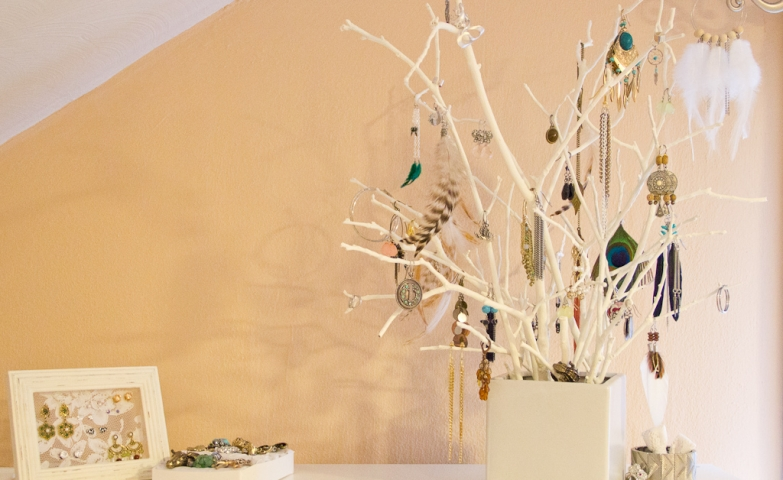 Creative jewelry display ideas using photo frames and branches placed inside a cube vase to hang different jewels on them.
