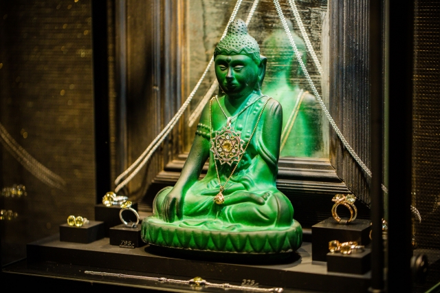Buddhist statue placed as a center piece for this jewelry display setting.