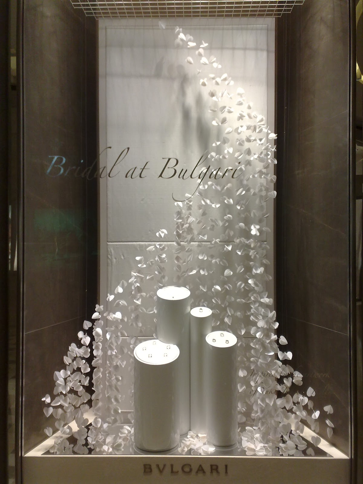 Beautiful Bulgari bridal window display with a curtain of white petals flowing upon the delicate jewelry pieces displayed.