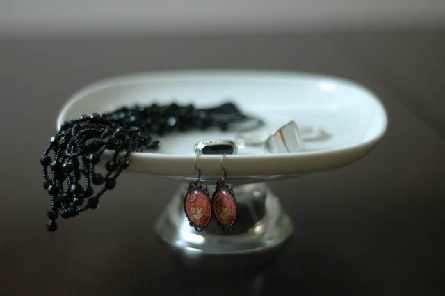 Small white holder with different pieces placed on it, inspiration from Miranda Hughes jewellery display.