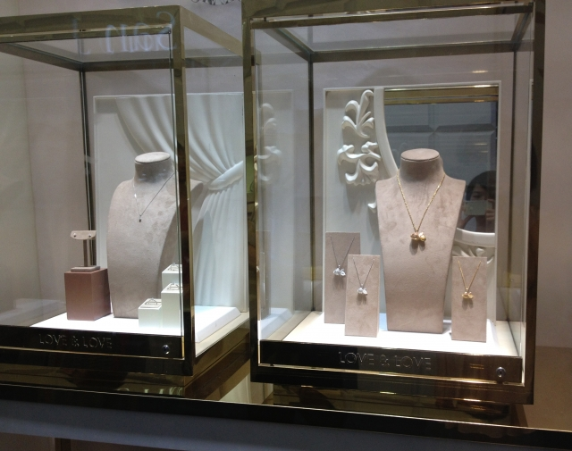 """""""Love & Love"""" collection by Cartier, jewelry display inside glass boxes with gold metal frame."""