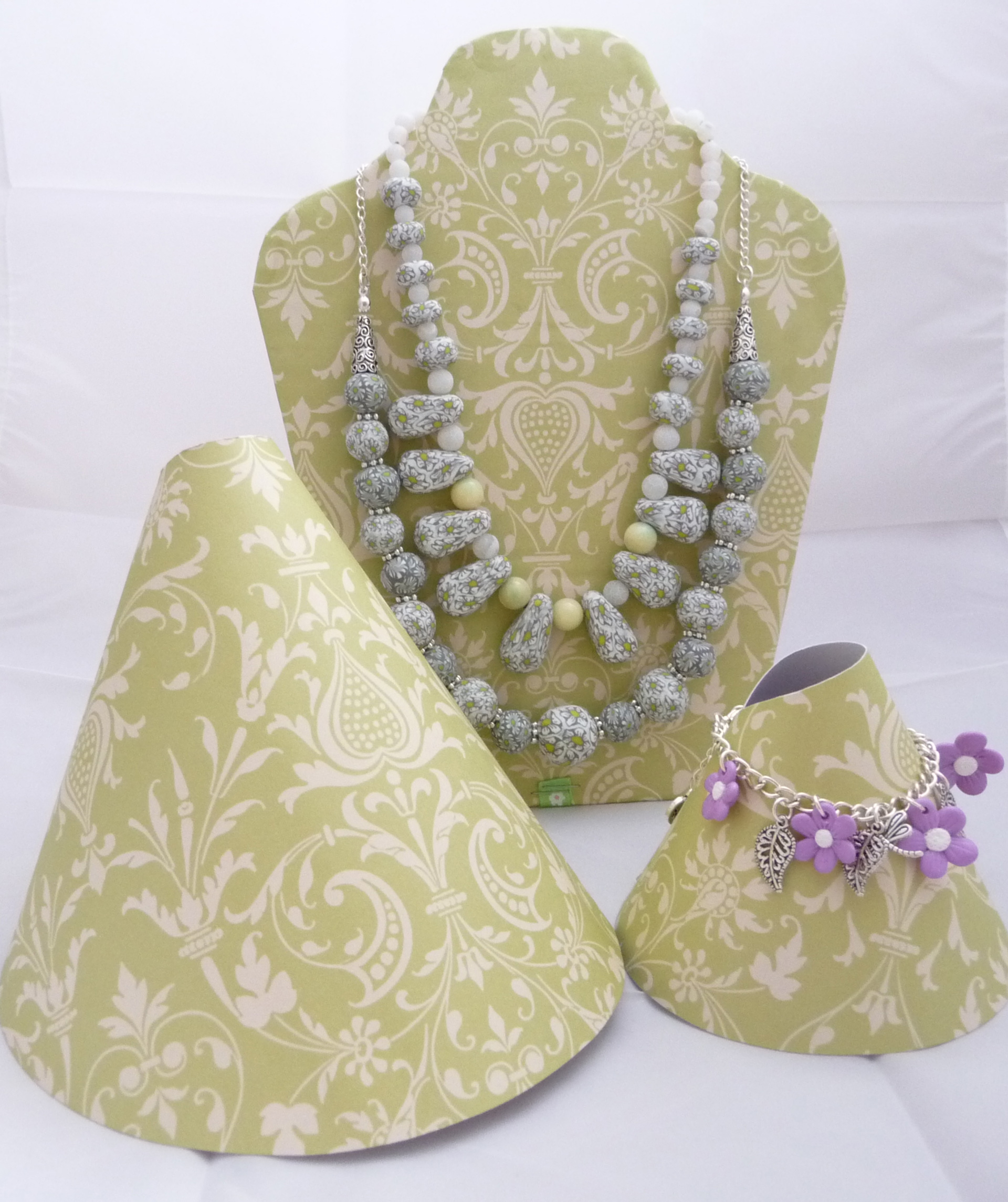 Necklace display ideas using holders made from tick paper with beautiful motifs and cut or bent different forms.