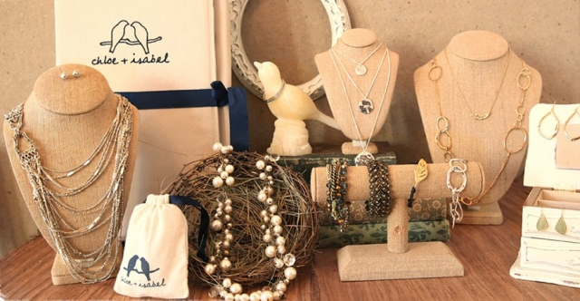 Setting for a neckline and burlap jewelry display with a holder in the shape of a bird and nest like prop, along different holders for necklaces and rack for bracelets.