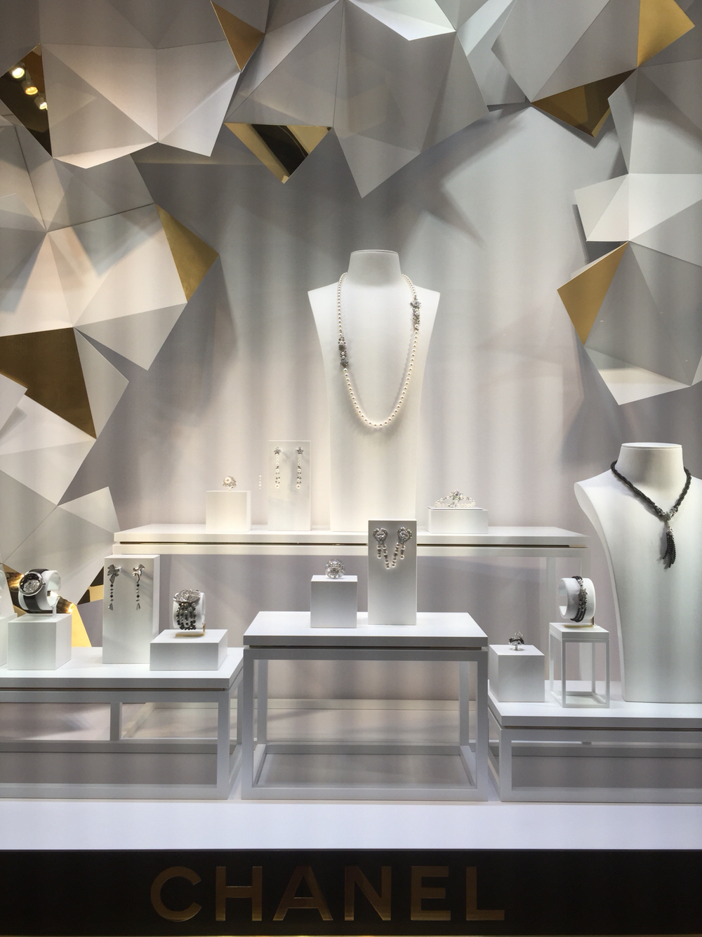 Modern jewelry display setting with geometric shapes in the background for the Chanel window display at Encore Hotel.
