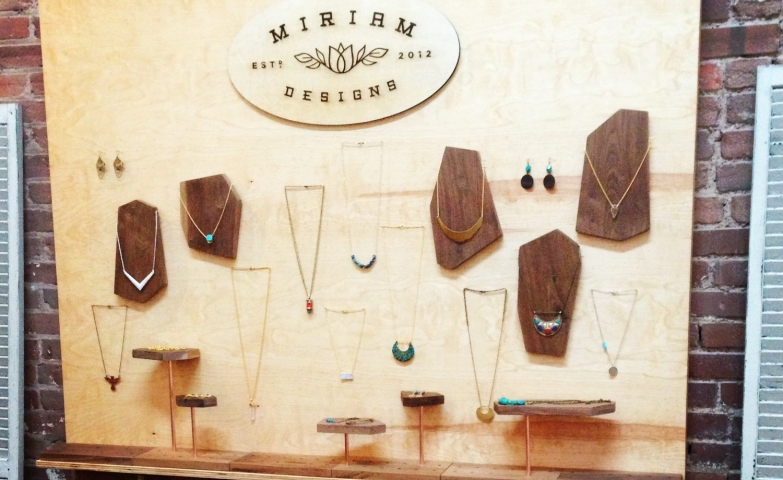 Copper pipe jewelry from Miriam Designs on a wooden wall mounted board with detachable stands and holders, creative jewelry display ideas.