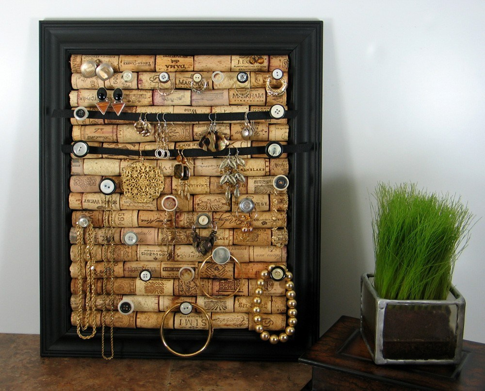 Cork board jewelry organizer inside a photo frame with knobs and buttons placed on it to hang jewelry, for creative DIY jewelry display ideas.