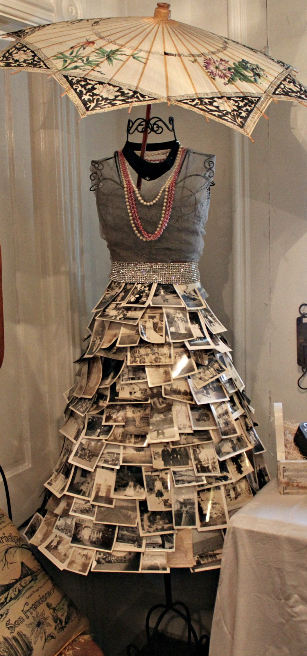 Creative craft ideas using a fitting bust with a skirt made from photos and necklaces around the neck, for unique jewelry display ideas.