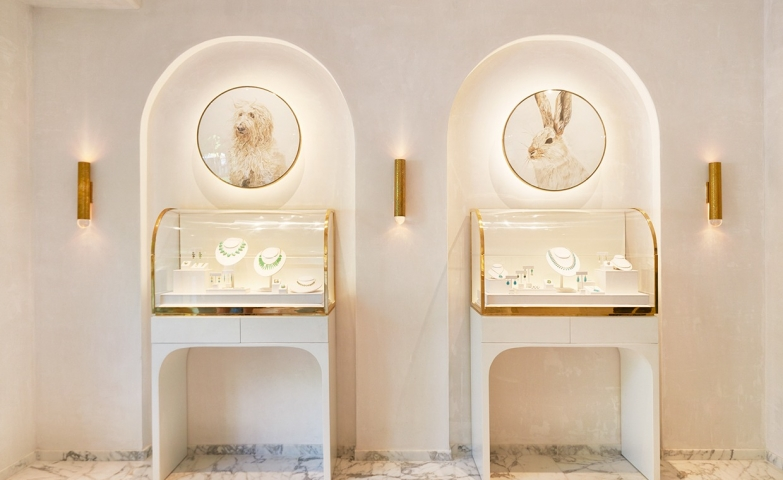 Private jewelry display with glass boxes and gold details. The two pictures of a dog and a rabbit add an original touch to it.