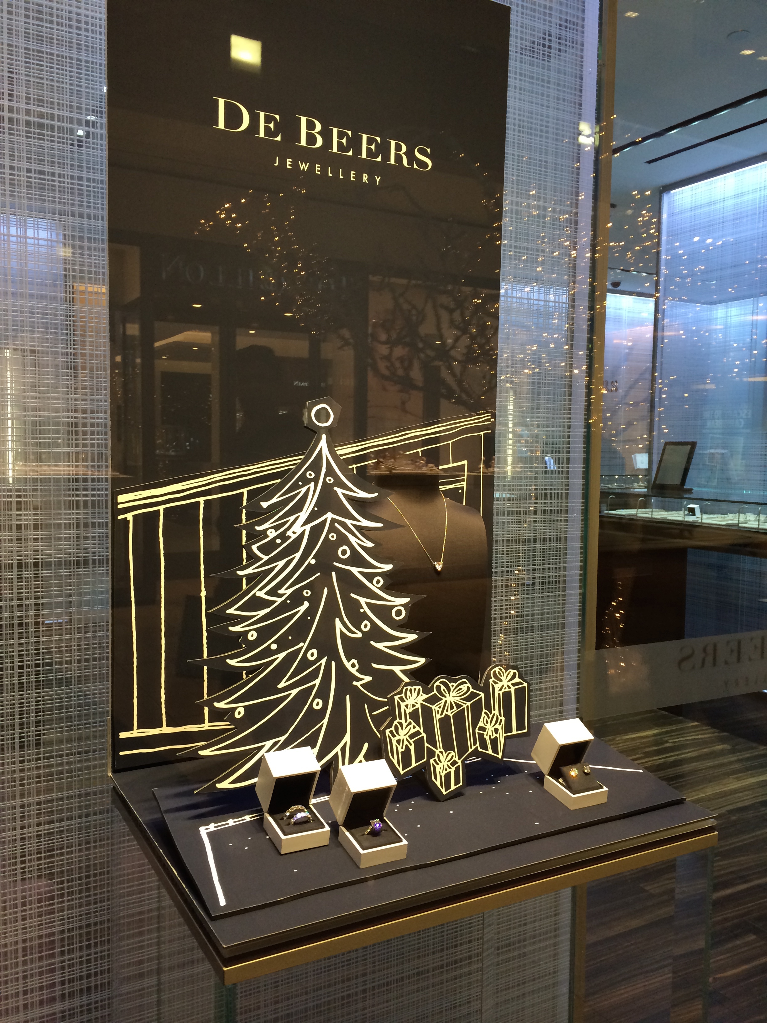 More jewelry display ideas for the holiday season with a simple illustration of a Christmas tree and presents around it, bu De Beers.