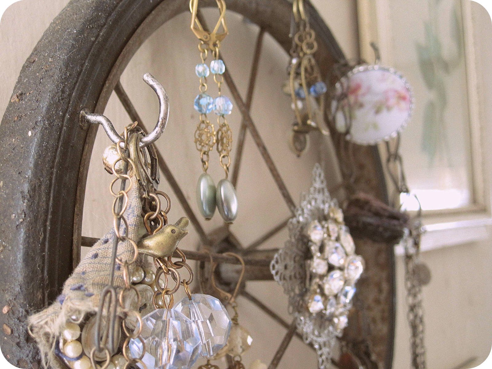 Shabby chic jewelry storage and display idea made from an old rusty wheel for hanging all kinds of jewels.