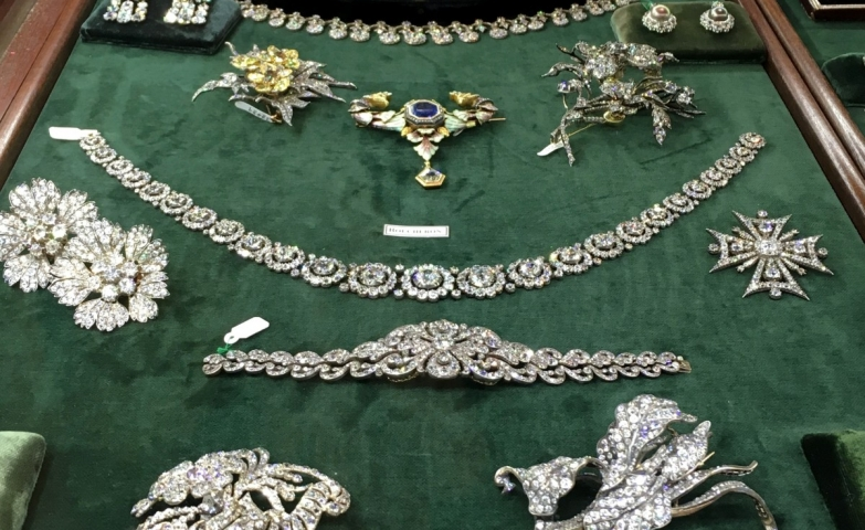 An antique diamond jewelry selection displayed on green velvet. The pieces are so stunning and unique that the jewelry display was kept simple.