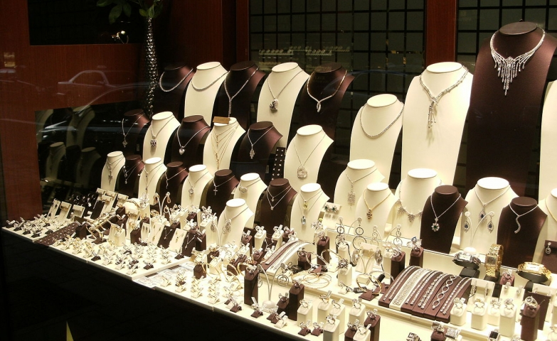 A shop window filled with necklace holders and all kinds of jewelry, a nice idea for selling jewelry in your display.