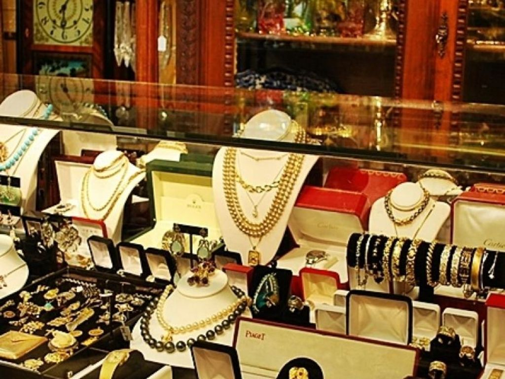 Unique jewelry store display with many jewels left inside the boxes and displayed directly with them, but also many jewels displayed on holders and racks.