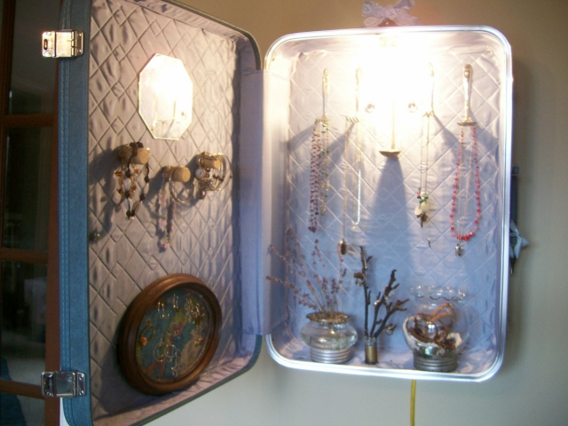 Upcycled vintage suitcase re-purposed to be used as a jewelry cabinet hanged on the wall.