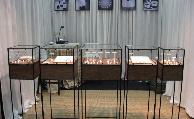 Genevieve Yang display booth, a jewelry display idea created with glass box displays on a wood base all placed on a metal wire stand.