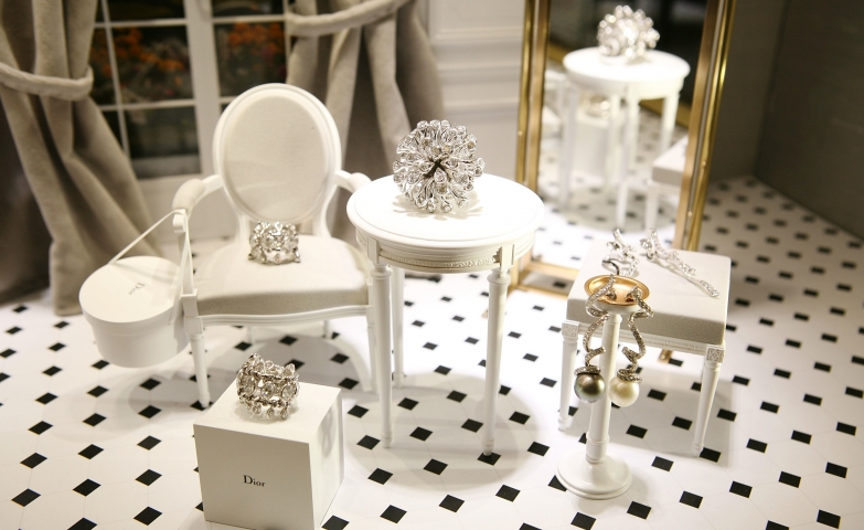 Window display and visual merchandising by Dior, using small doll furniture to create a setting and display the jewels on the furniture.