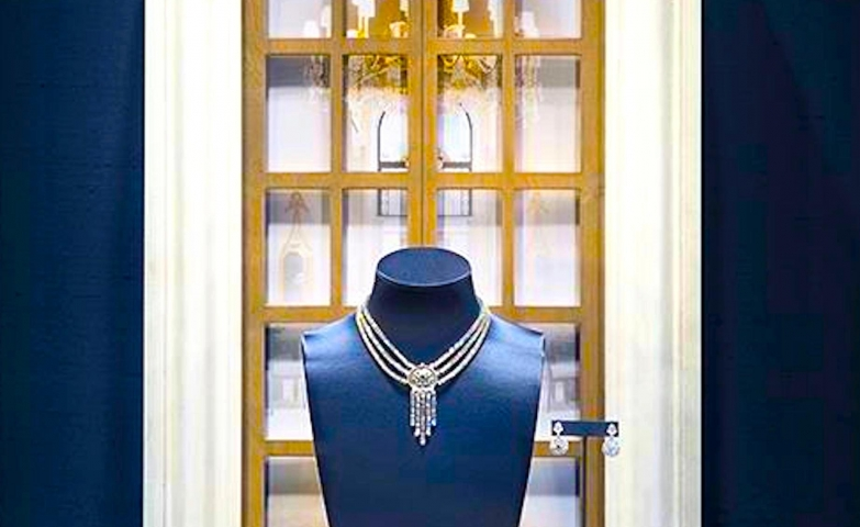 Harry Winston visual merchandising windows with a royal blue theme and an antique window in the background, inspiration for jewelry display ideas.