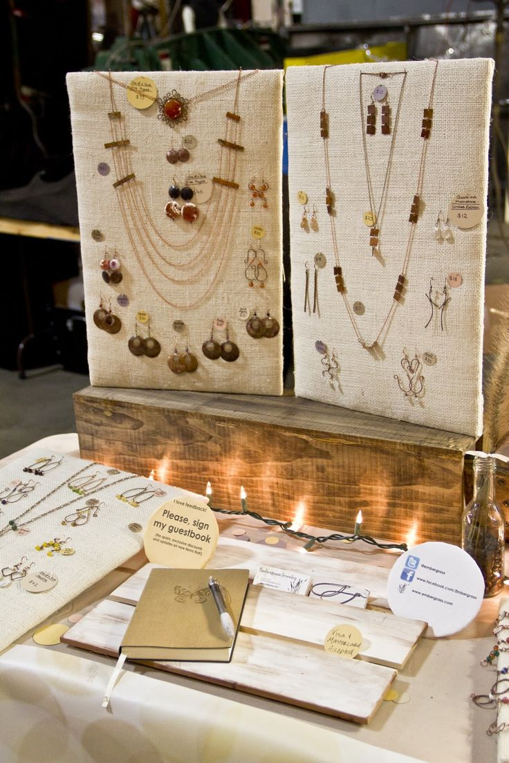 Ideas for jewelry craft fair display using boards with a cloth on them to hang the jewelry, lights and a notebook for a simple decor.