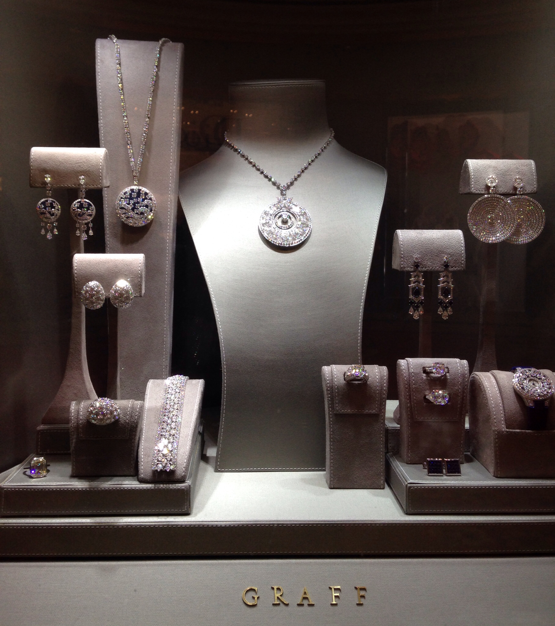 Stands and visual merchandising ideas from the window display of a jewelry store, grey set for diamond jewelry display.