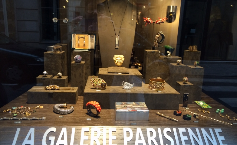 Big wood stand and smaller stand pieces on different levels with all kinds of jewelry displayed on them, jewelry display ideas from La Galerie Parisienne.