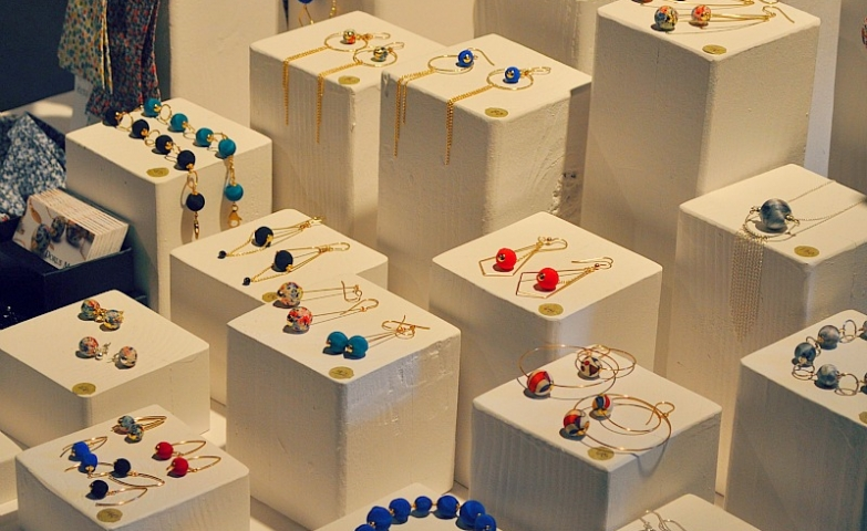 Lovely eye-catching way to display jewellery at a craft market using small white stands on different levels, a great display idea for colorful jewelry.