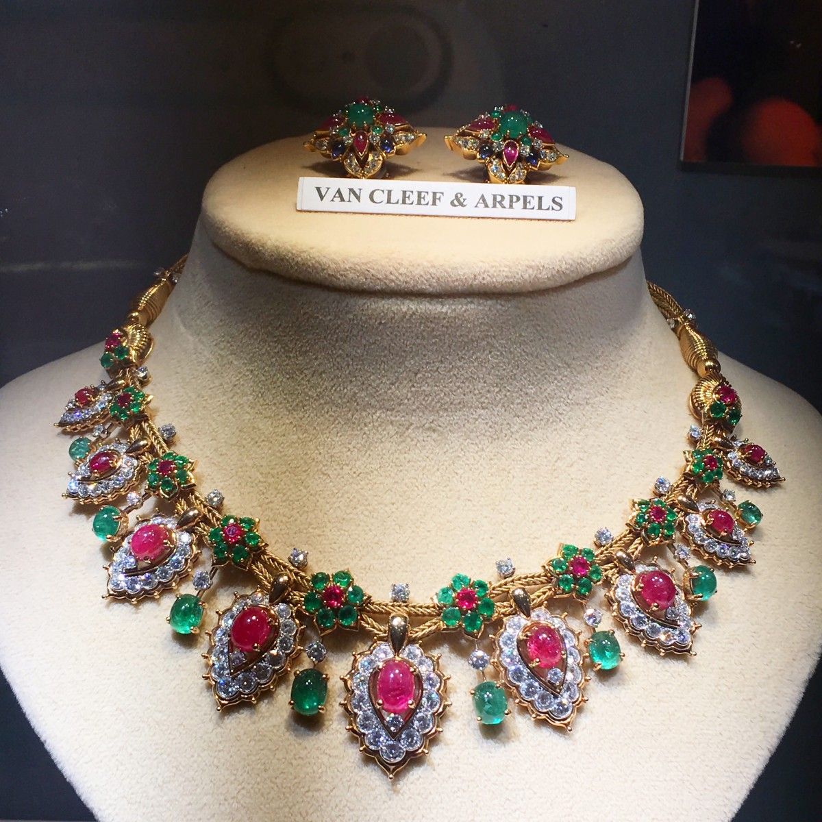 Magnificent set of ruby, emerald and diamond necklace with matching earring displayed on a necklace holder by Van Cleef and Arpels.