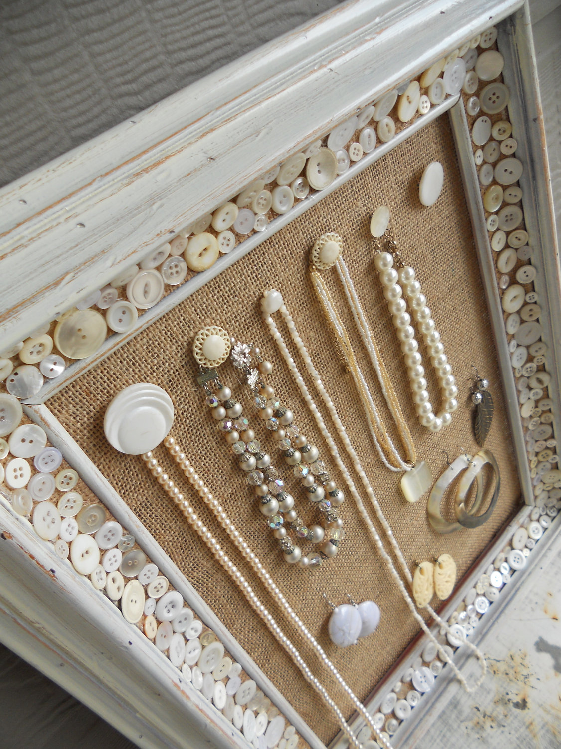 Jewelry display ideas using a photo frame with a board or simply just a cloth secured in the background, and different knobs placed on it for hanging necklaces and earrings, a great idea for a display stand.