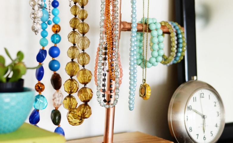 Diy necklace holder stand made from a block of wood and copper pipes for hanging necklaces and bracelets.