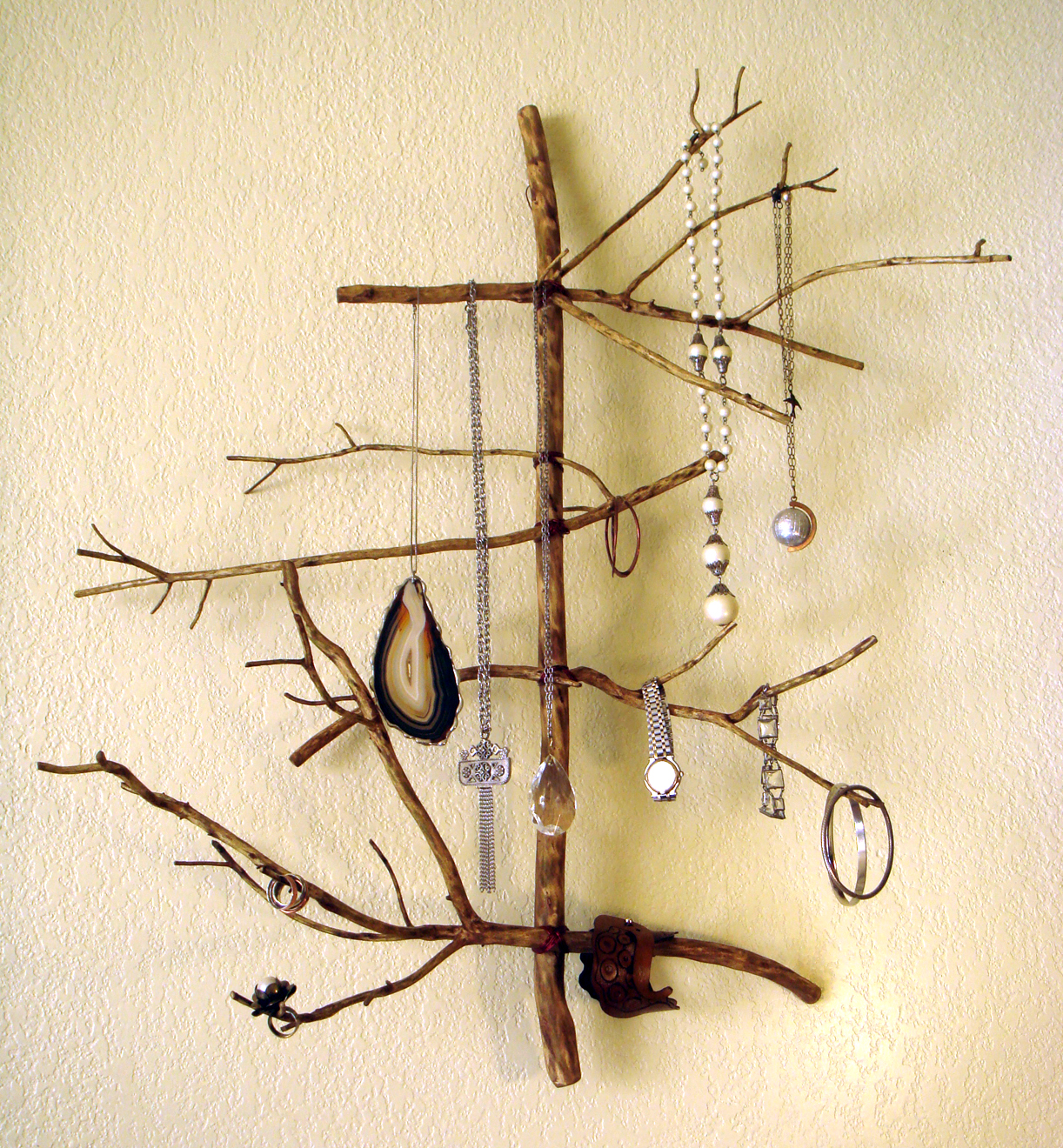 Diy rustic wooden jewelry hanger for wall, made from twigs. Creative jewelry display or jewelry storage ideas.