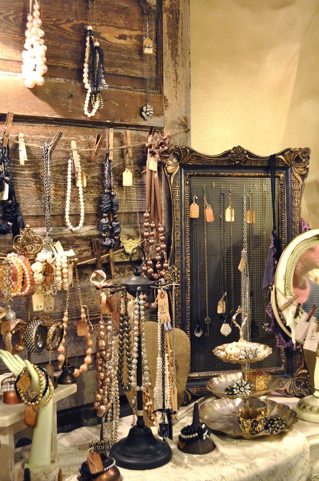 Rustic themed jewelry display, with jewelry hanged on a door like wood piece, on a rope with clothes hangers, on a photo frame and other display pieces.