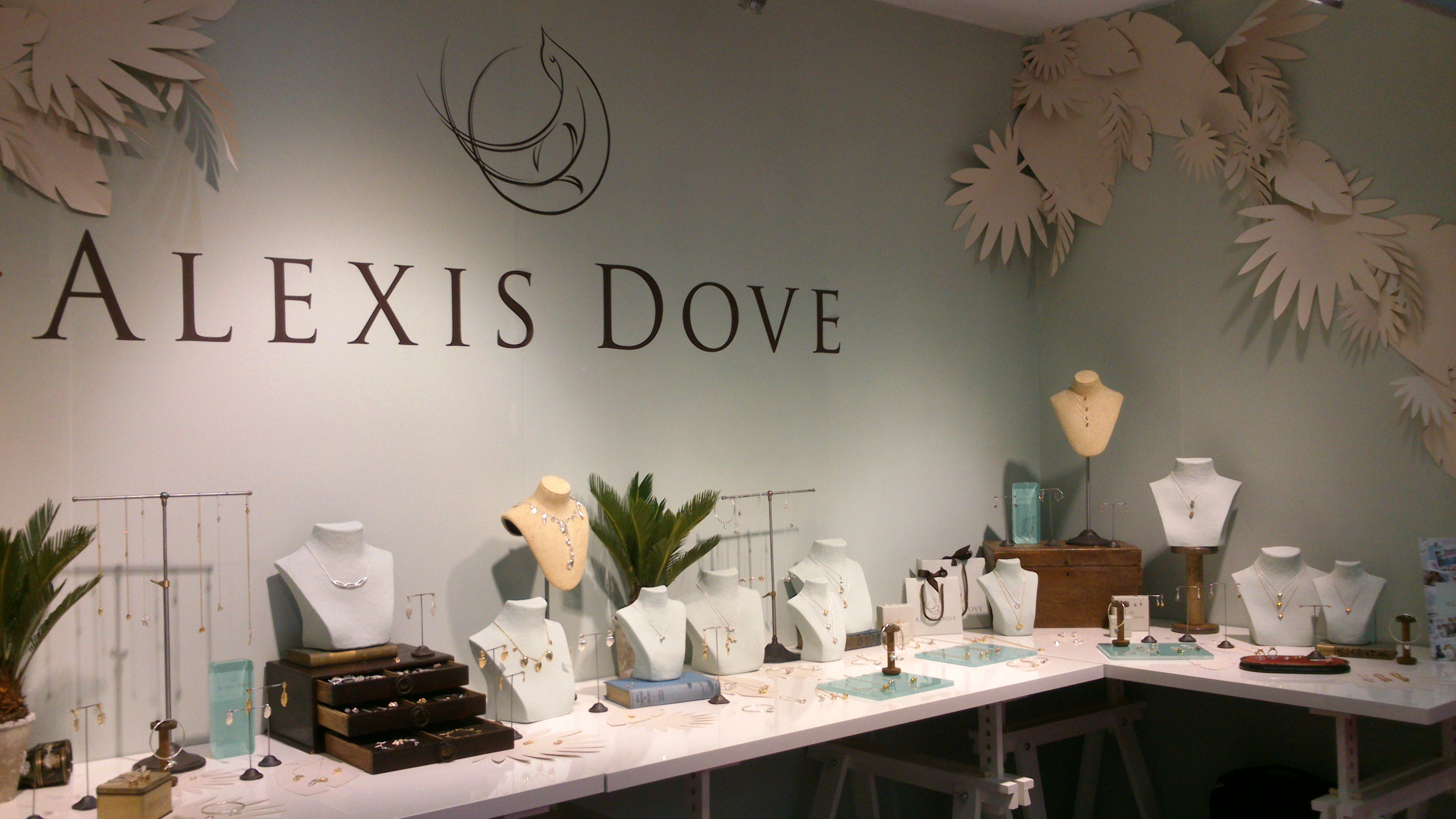 Alexis Dove inspiration for jewelry display store ideas. A setting with decor including small plants and paper leafs on the walls.