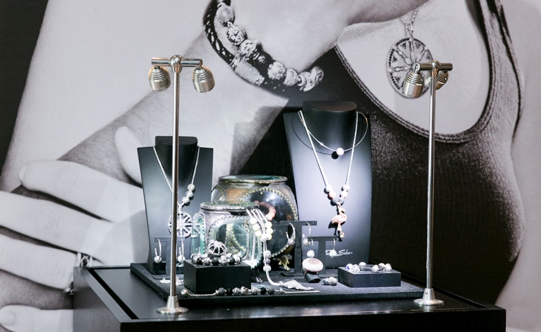 Pearl ring and sterling silver pieces, window display with ad photo in the background for Thomas Sabo.