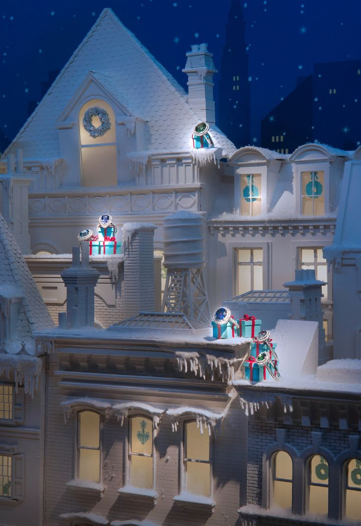 Tiffany & Co Christmas setting with buildings and houses, all white to give the impression of snow and winter, and small present boxes on the rooftops on which the jewelry is displayed.