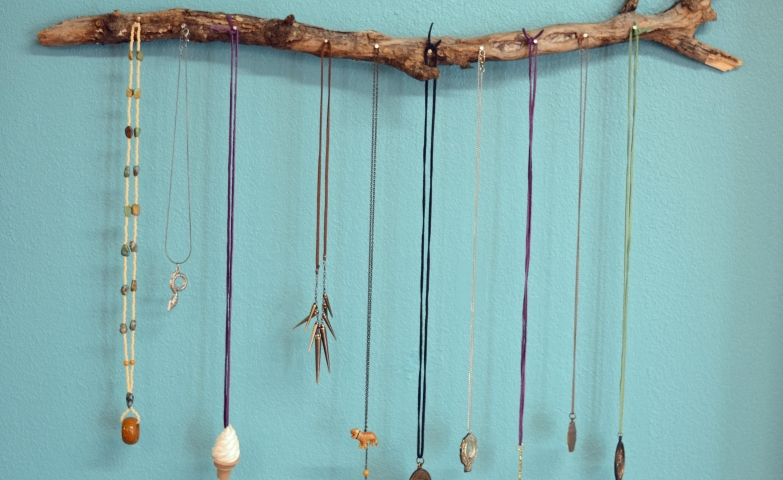 Jewelry display ideas for a diy tree branch jewelry holder with nails to hang the necklaces on it.