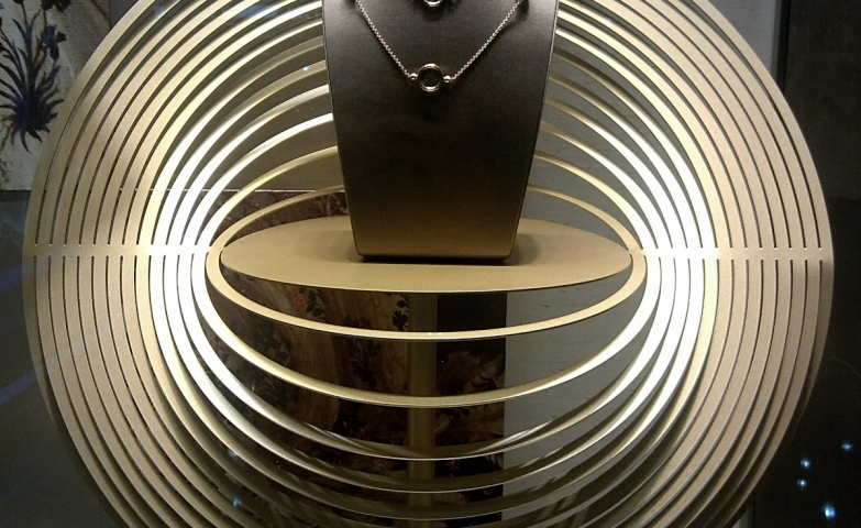 Space themed jewelry display showing a black necklace holder on a round stand with various circles around it almost creating an optical illusion.