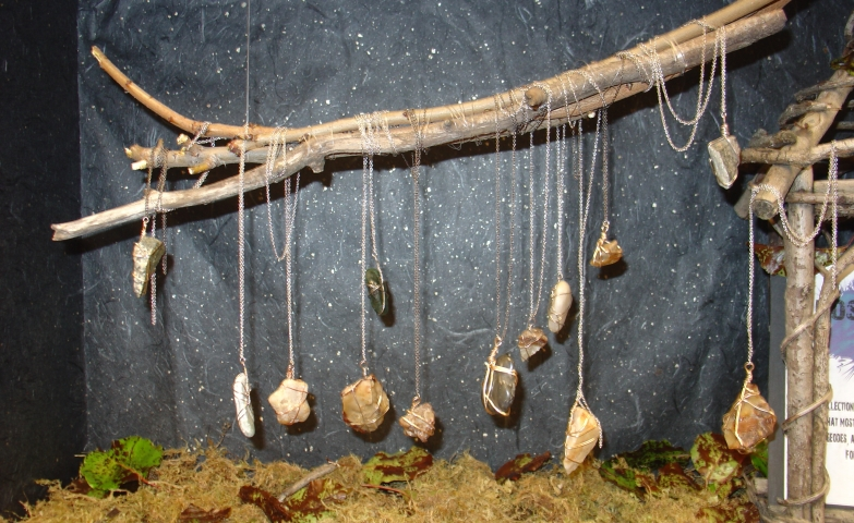 Natural jewelry display design idea and visual merchandising ideas for jewelry made with natural stones. Display created with tree branches, musk and a galaxy background.