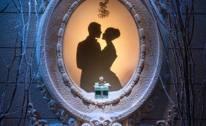 Visual merchandising and jewelry display ideas for the holiday season showing a couple about to kiss underneath the mistletoe, and in the center a beautiful ring placed on a small gift box.