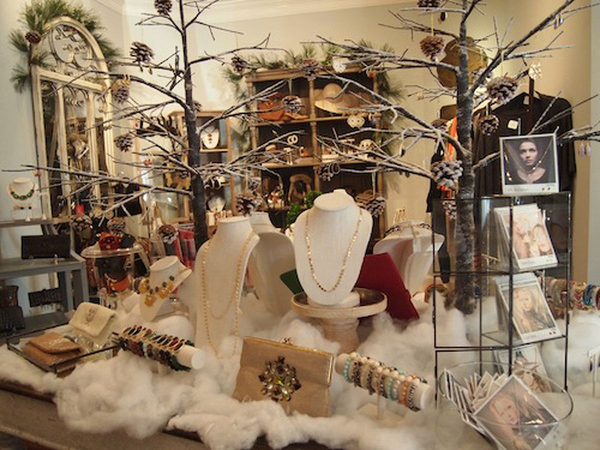 Window store display using cotton, small natural trees and pinecones to create a dreamy forest look. Inspiration for window store and jewelry display ideas.