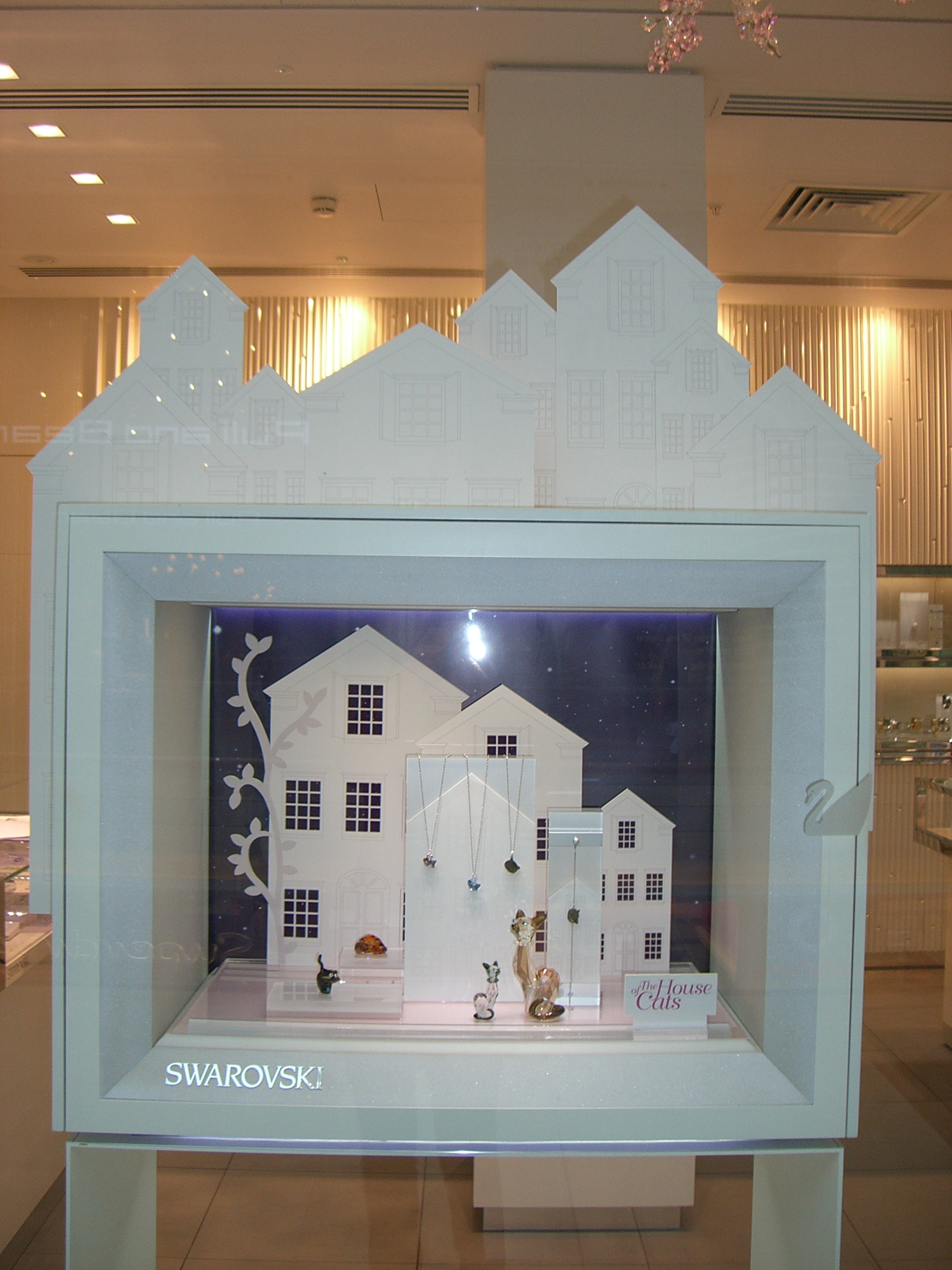 Swarovski jewelry display setting based on a house theme. Jewelry displayed in a box, with houses on top of it and also inside the box. Original ideas for jewelry display.