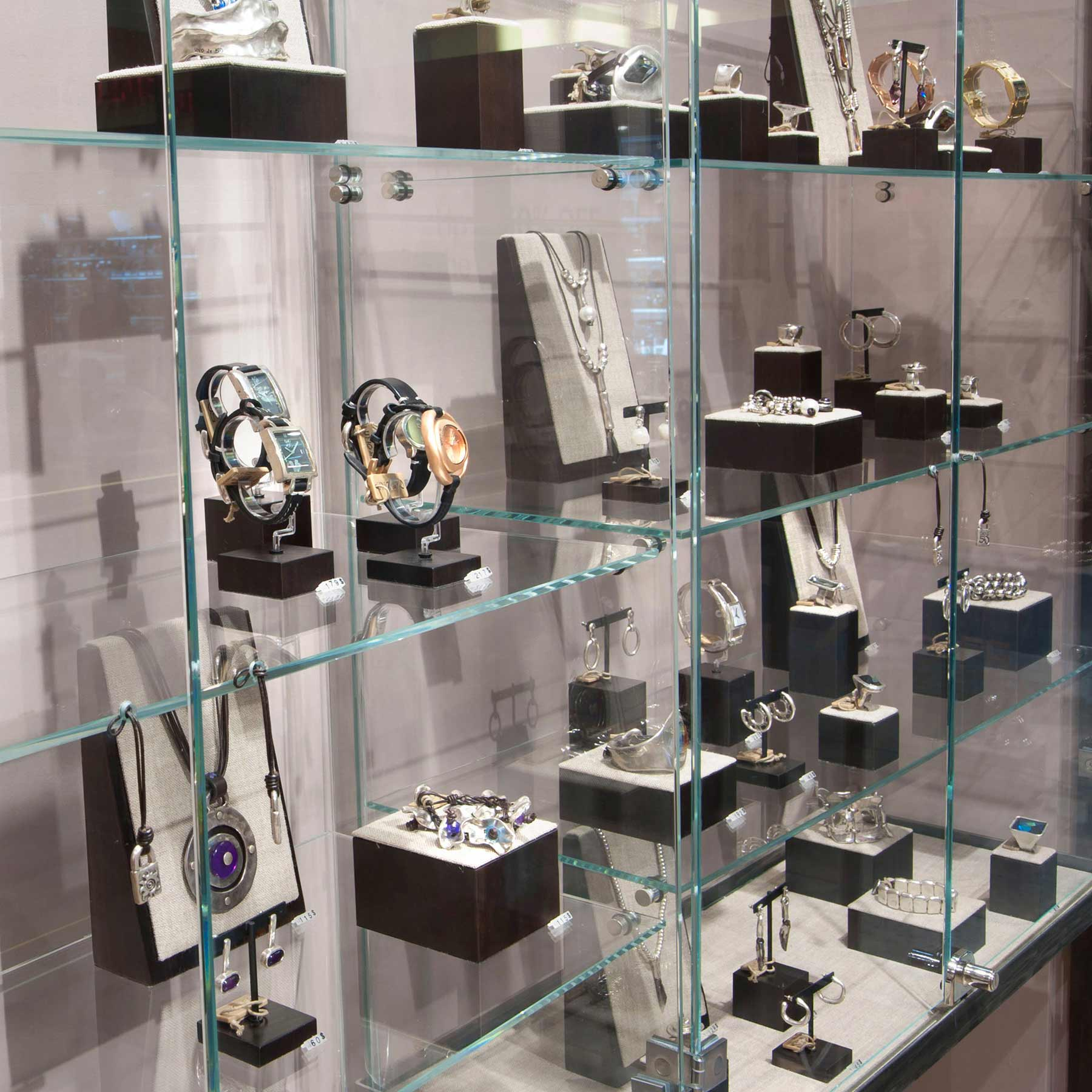 Glass shelves with black & white stands and holders for different types of jewelry, seen at jewelry displays across Miami.